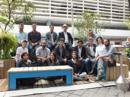 Grupo de amigos se reúnem em espaço de convivência com bancos e floreiras, em São Paulo.